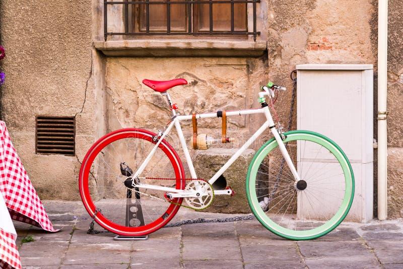 Bicykl z kolorami włoszczyzny flaga obok ściany wewnątrz zdjęcia stock