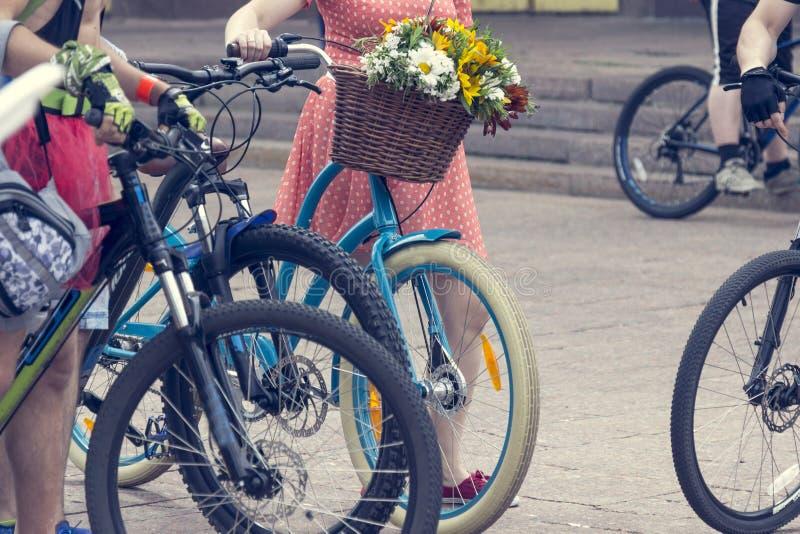 Bicykle z koszami kwiaty Kobiety w jaskrawych ubraniach trzymają handlebars obrazy stock