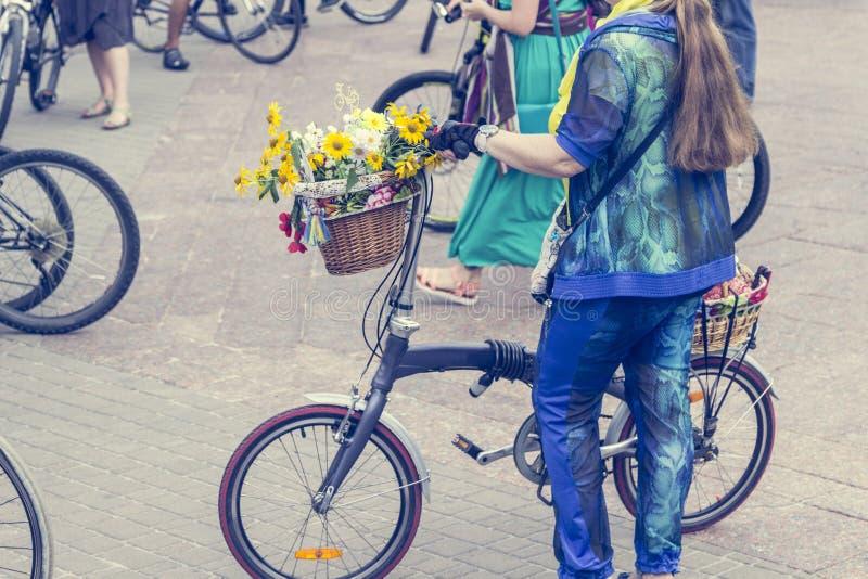 Bicykle z koszami kwiaty Kobiety w jaskrawych ubraniach trzymają handlebars zdjęcia royalty free