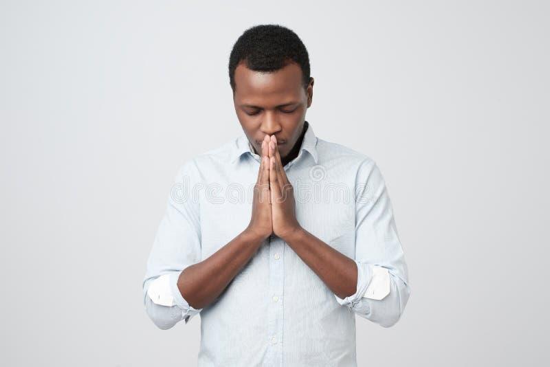 Biddend de Afrikaanse Amerikaanse mens die beter hopen voor stock afbeelding