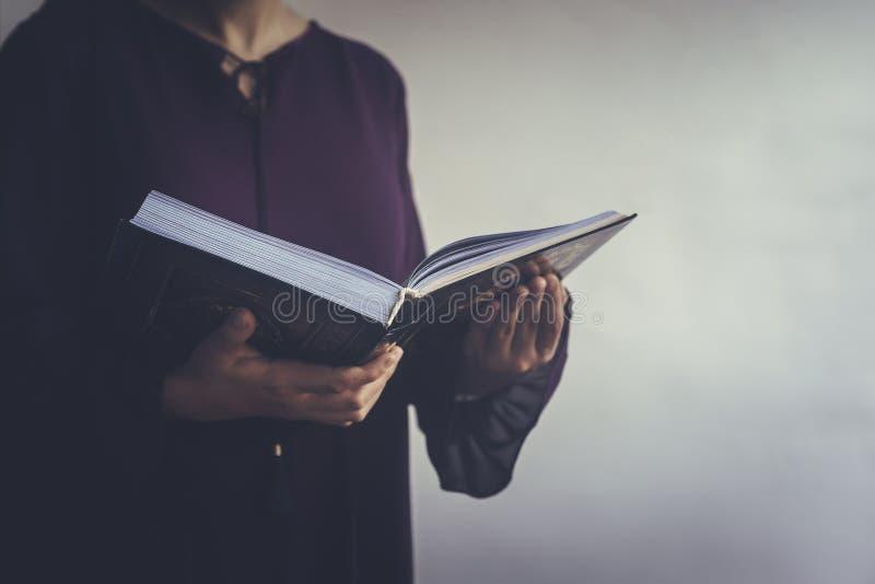 Biddende jonge moslimvrouw Meisje dat van het Middenoosten en heilige Quran bidt het leest Moslimvrouw die Quran bestuderen stock fotografie