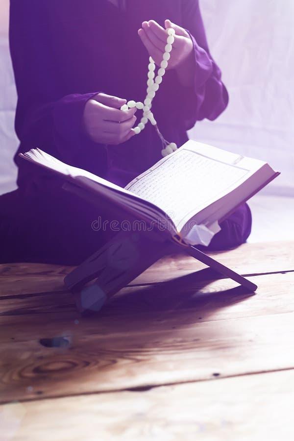 Biddende jonge moslimvrouw Meisje dat van het Middenoosten en heilige Quran bidt het leest Moslimvrouw die Quran bestuderen royalty-vrije stock fotografie