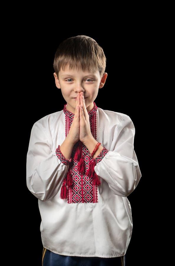 Biddende jongen in traditionele Oekraïense kleren royalty-vrije stock foto's