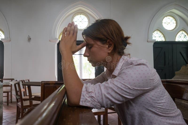 Biddende vrouw in christelijke kerk biddende God voor hulp stock afbeelding