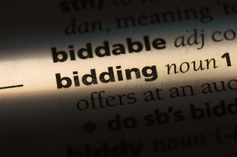 Bidding. Word in a dictionary.  concept royalty free stock photo