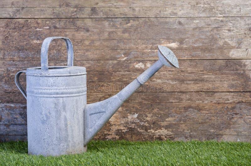 Bidon d'arrosage sur l'herbe contre un mur en bois photo libre de droits