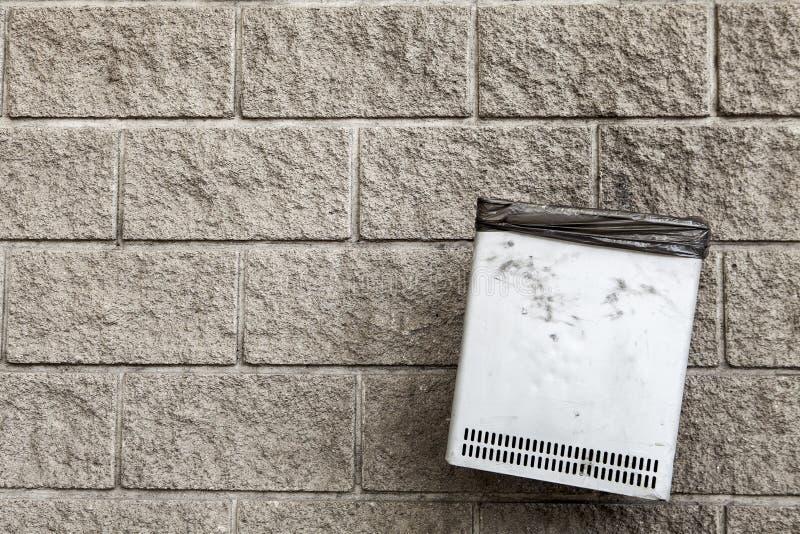Bidone della spazzatura appeso su un fondo del muro di cemento fotografia stock