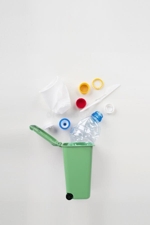 Bidone della spazzatura con spreco di plastica su un fondo grigio Riciclaggio del concetto immagine stock