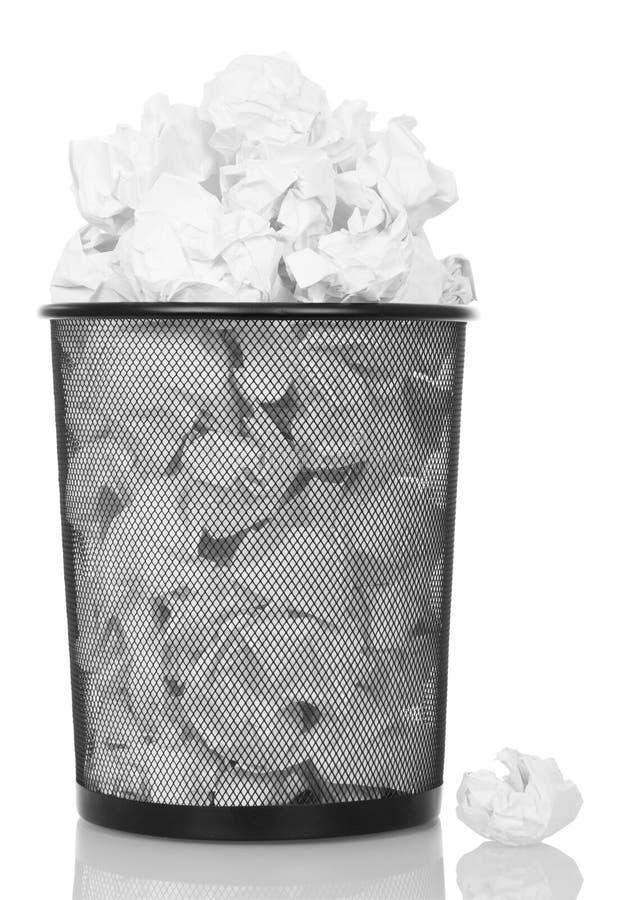 Bidone della spazzatura di straripamento del metallo da carta isolata su bianco immagine stock