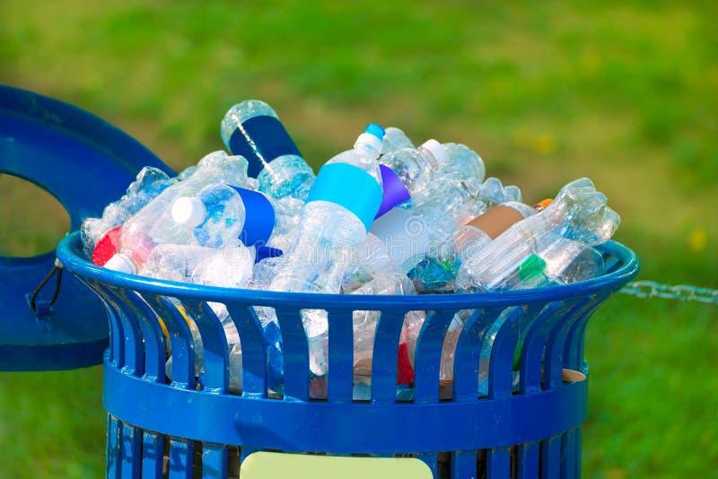 Bidone della spazzatura in pieno delle bottiglie vuote della bevanda immagine stock