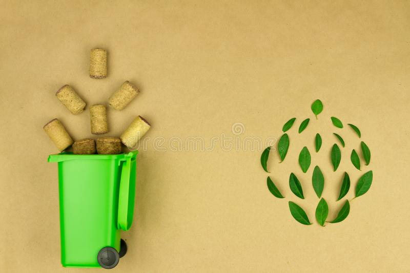 Bidone della spazzatura verde con i sugheri di legno del vino fotografia stock