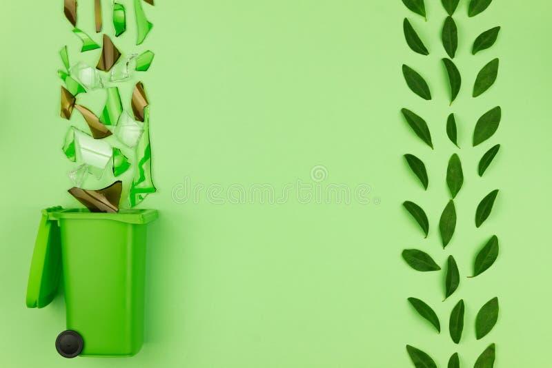 Bidone della spazzatura verde con vetro rotto immagini stock