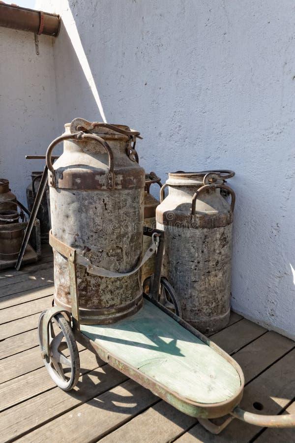 Bidons à lait de vintage avec le chariot photographie stock libre de droits