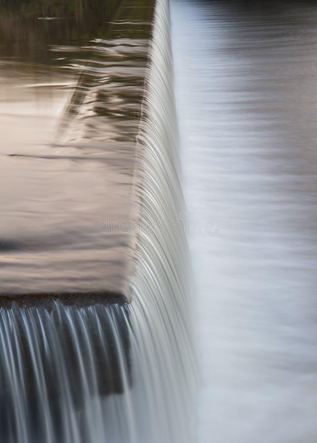 Bieżąca woda spada kaskadą nad jazem na Yorkshire rzece zdjęcie stock