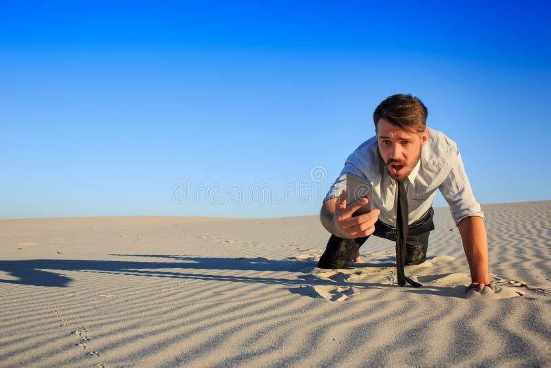 Bieda sygnalizuje biznesmena gmeranie dla telefonu komórkowego sygnału w pustyni fotografia stock