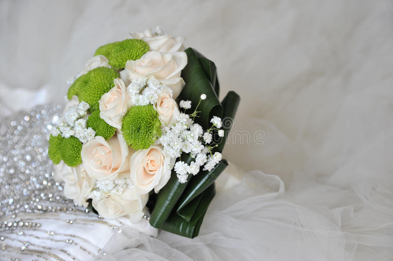 Biedermeier Flowers. Biedermeier bridal bouqet with white and green flowers and wedding dress in background royalty free stock images