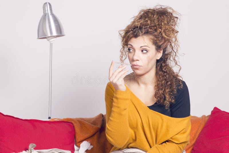 Biedna chora kobieta, bierze jej temperaturę z termometrem zdjęcia stock