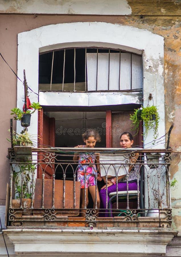 Biedna kubańczyk matka i dziecko zdobycza portret w tradycyjnej kolorowej alei z starym kolonisty domem w stary Hawańskim, Kuba,  zdjęcia stock