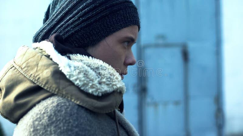 Biedna m?oda kobieta w kapeluszu i kurtki bocznym widoku, bezdomna osoba outdoors, ?ebrak zdjęcia stock