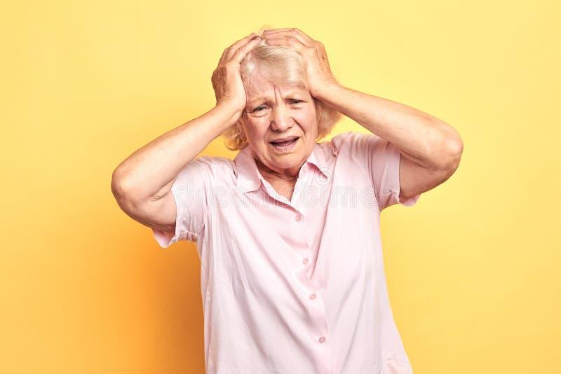 Biedna starsza kobieta migrenę, ona dotyka jej głowę z paalms zdjęcia royalty free