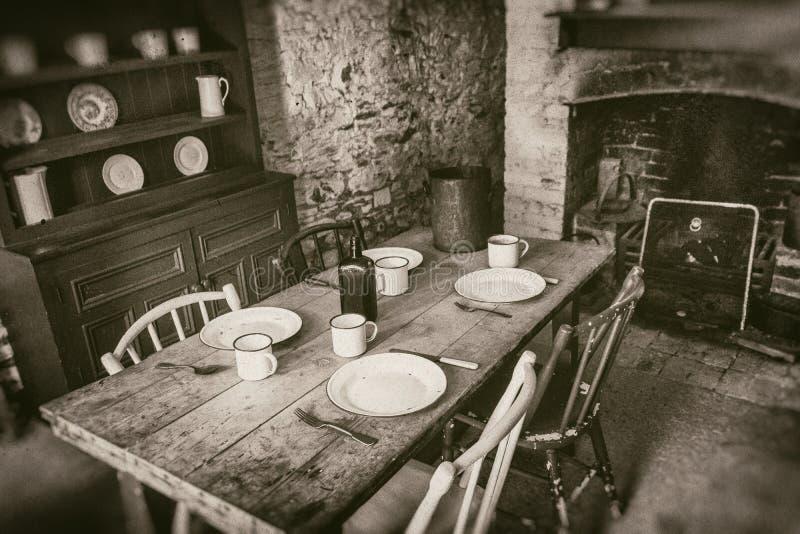 Biedni chłopi wewnętrzni od xix wiek, jadalni z ustalonym drewnianym stołem i graby, sepiowa stylowa fotografia obraz stock