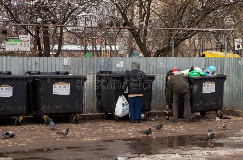 Biedni ludzie bezdomni zbierają butelki blisko kubeł na śmieci zdjęcia royalty free