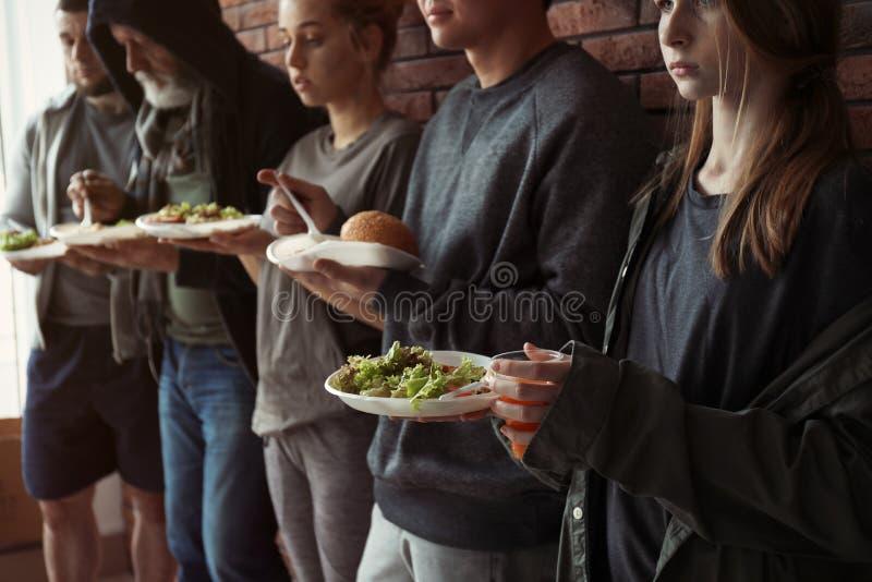 Biedni ludzie z talerzami jedzenie przy ?cian? obraz royalty free