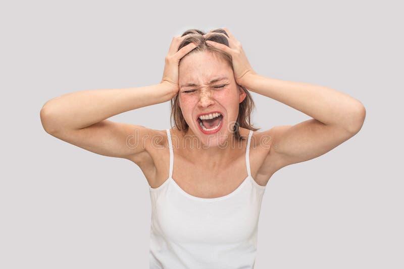 Biedni młoda kobieta stojaki, cierpienie od okropnej migreny i Krzyczy Model utrzymuje oczy zamyka Jest ubranym białego t zdjęcie royalty free