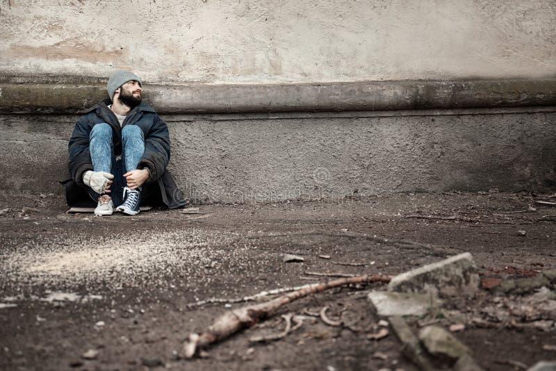 Biedny bezdomny mężczyzna siedzi blisko ściany na ulicie obraz stock