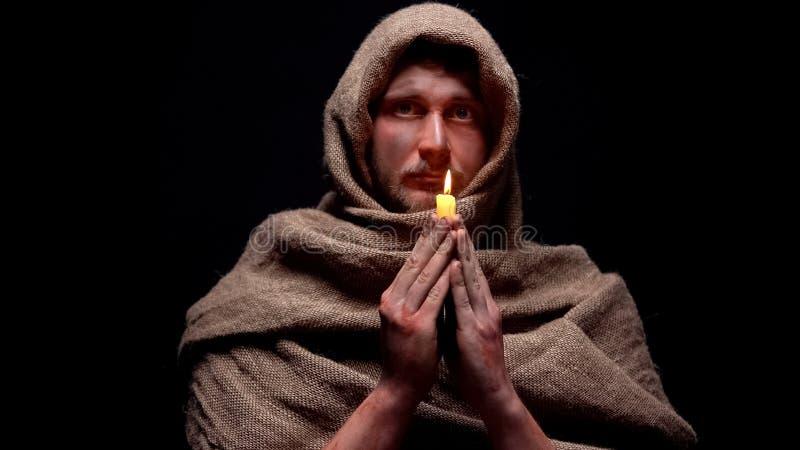 Biedny chory mężczyzna trzyma świeczkę i modli się boga w kontuszu, pyta dla pomocy, wiara zdjęcia stock