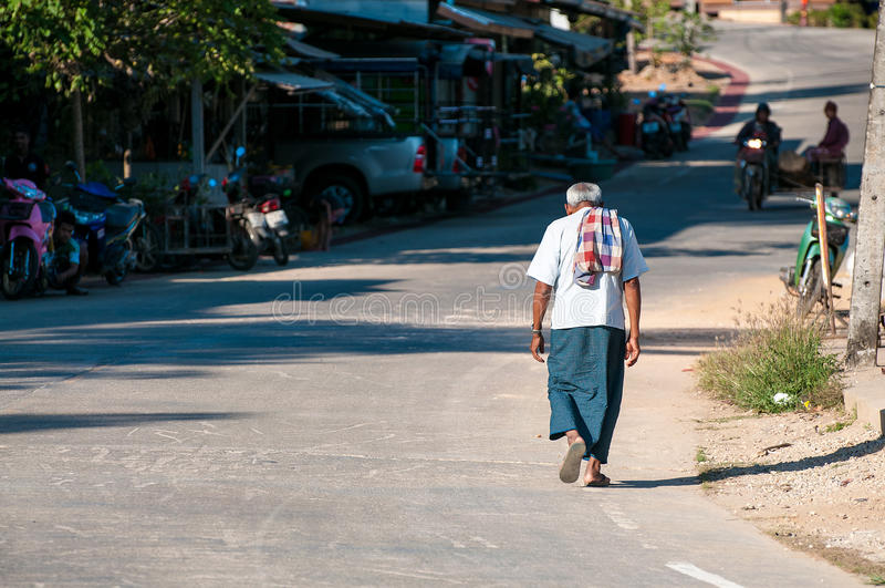 Biedny humpback starego człowieka odprowadzenie w egzotycznej azjatykciej ulicie obraz stock
