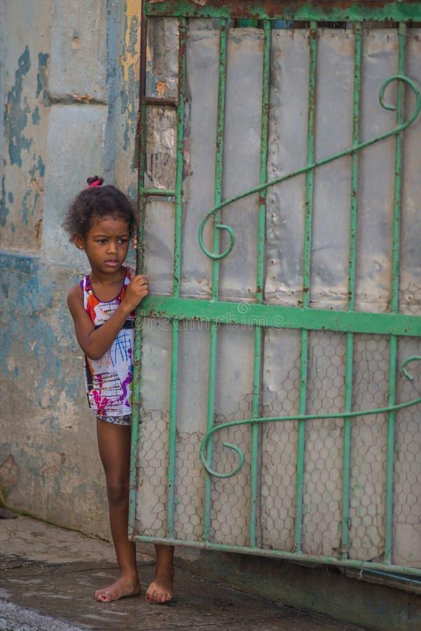 Biedny Kubański dziewczyna zdobycza portret w tradycyjnej kolorowej kolonialnej alei z starym życie stylem w stary Hawańskim, Kub zdjęcie stock