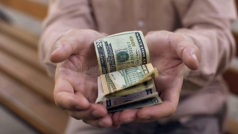Biedny męski emeryt pokazuje few dolarowych rachunki w rękach, kryzys gospodarczy, potrzeba obraz stock