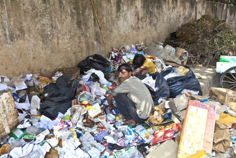 Biedny pracownik sprawdza śmieci dla zdjęcia stock