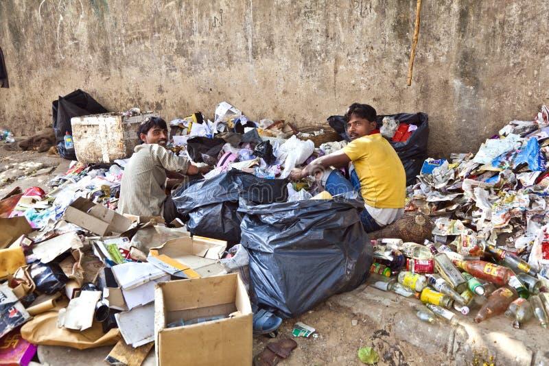 Biedny pracownik sprawdza śmieci dla obraz stock
