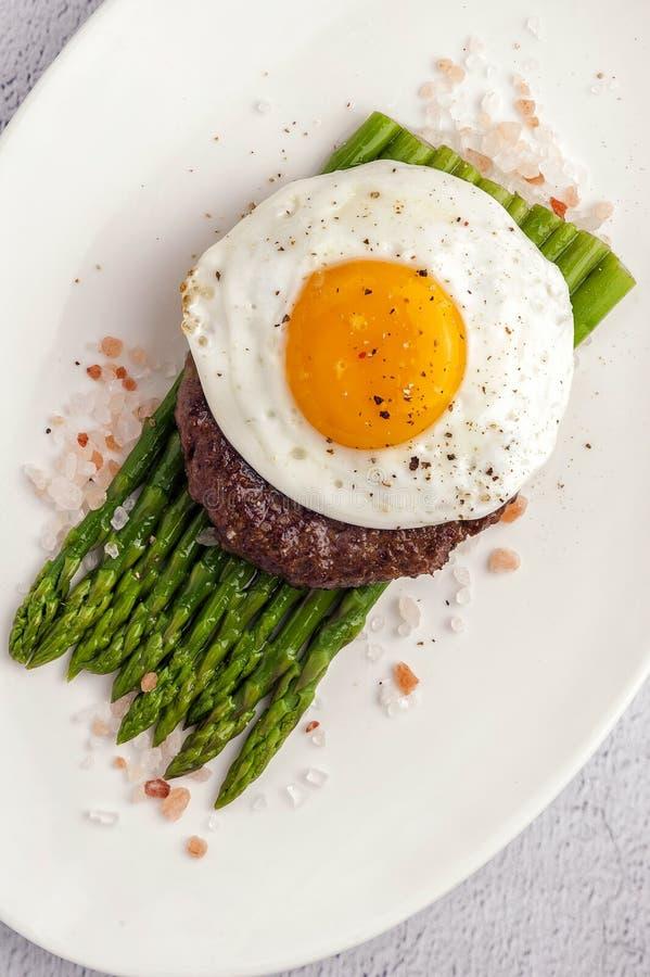 Biefstuk van fijngehakt rundvlees met gebraden eieren en verse groene asperge stock foto's