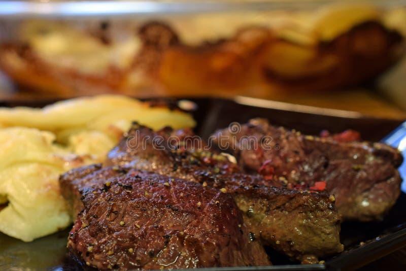 Biefstukken en romige gratinaardappels stock fotografie
