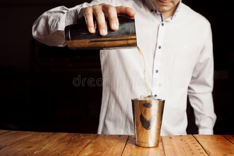 Biegły barman robi wyśmienicie koktajlowi na drewnianym baru kontuarze fotografia royalty free