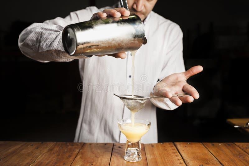 Biegły barman robi wyśmienicie koktajlowi na drewnianym baru kontuarze zdjęcie stock