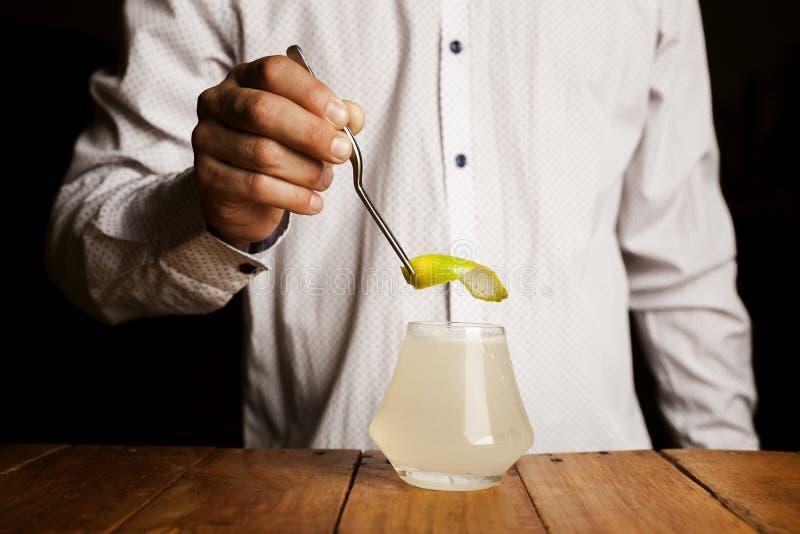 Biegły barman robi wyśmienicie koktajlowi na drewnianym baru kontuarze Zamyka w g?r? strza?u obraz royalty free