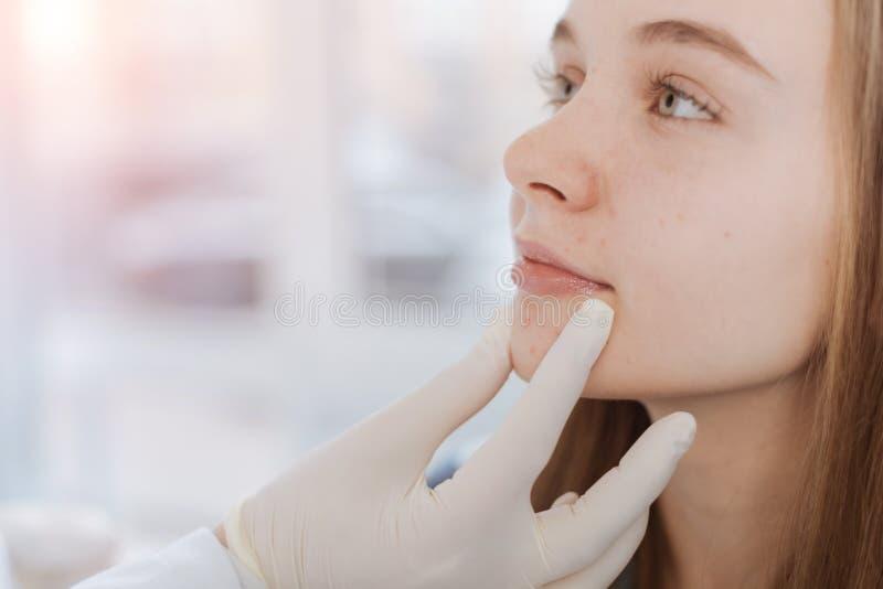 Biegły dermatolog egzamininuje cierpliwą twarz w klinice obraz stock