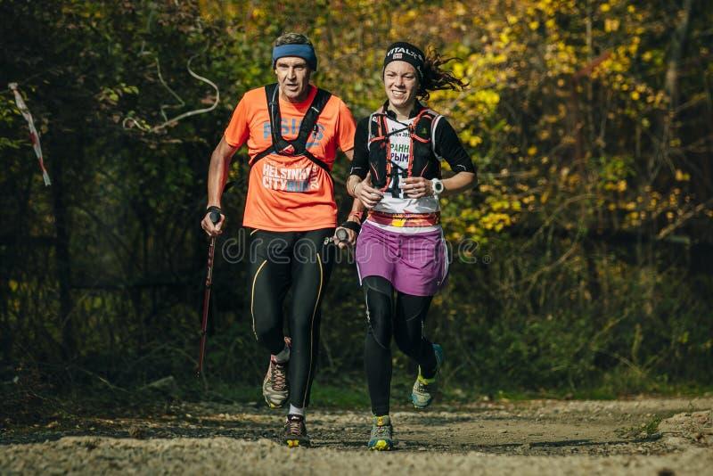 Biegać wzdłuż młodej kobiety w jesień lesie i starego człowieka obraz royalty free