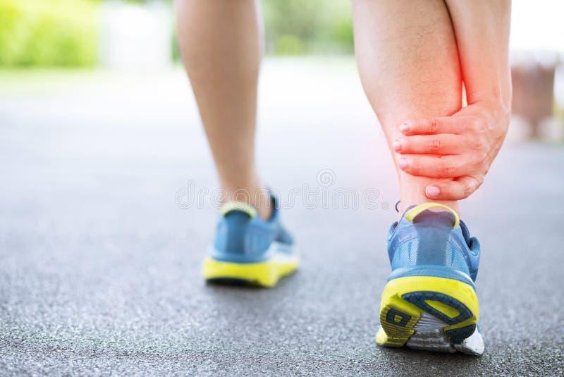Biegacz dotyka bolesn? kr?con? lub ?aman? kostk? Atleta biegacza sta?owy wypadek Sporta zwichnięcia przyczyny działająca kostka z obraz stock