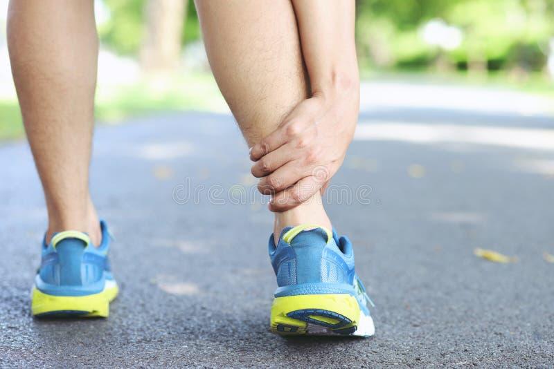 Biegacz dotyka bolesn? kr?con? lub ?aman? kostk? Atleta biegacza sta?owy wypadek Sporta zwichnięcia przyczyny działająca kostka z fotografia royalty free