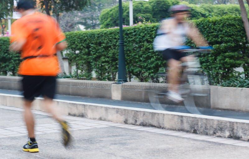 Biegacz i rowerzysta ćwiczymy w parku, ruch blured zdjęcie stock