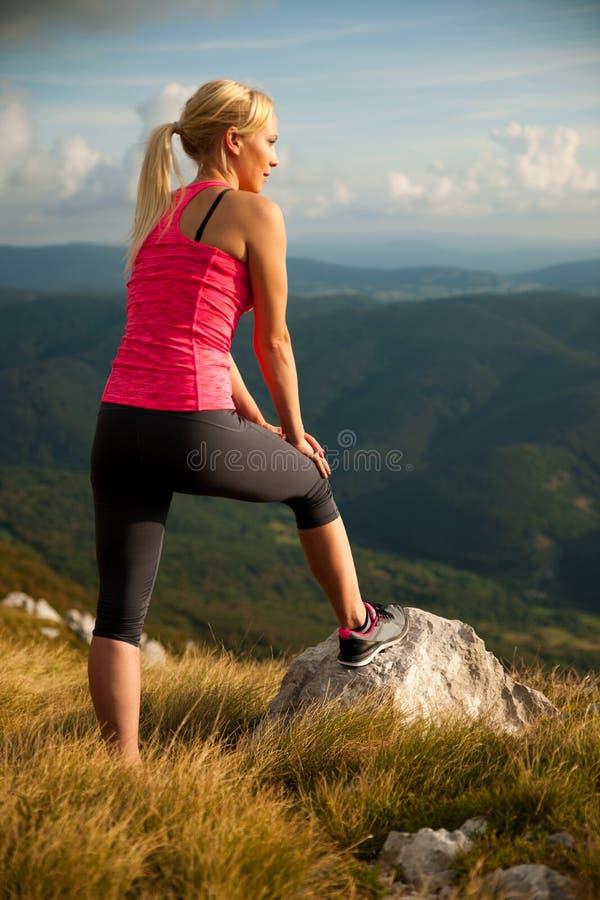 Biegacz kobieta odpoczywa na halnym wierzchołku po działającego treningu obraz stock