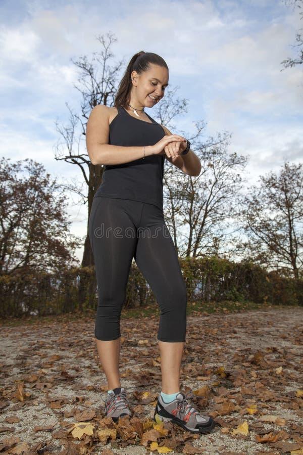 Biegacz kobieta sprawdza czasu i pulsu tempo obrazy stock