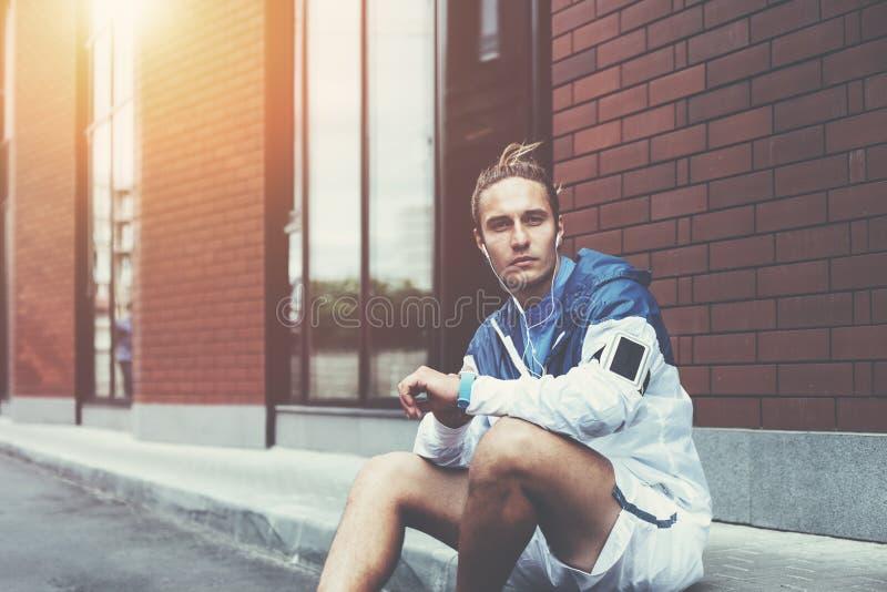 Biegacz w błękitnym obsiadaniu na ulicie zanim jego wczesnego poranku trening używać mądrze zegarki na jego ręka i armband z smar obrazy stock