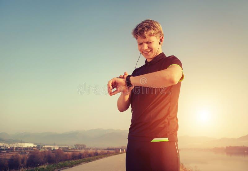 Biegacz zaczyna jego nowożytnego stopwatch przed jogging zdjęcia royalty free