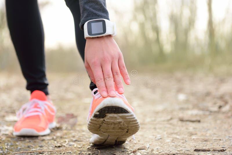Biegacza rozciągania noga przed bieg z smartwatch fotografia stock